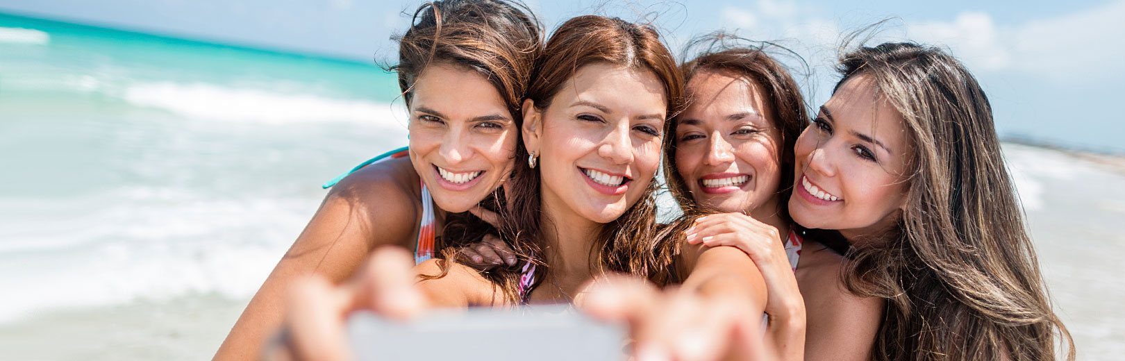 Girls smiling and taking a photo on the beach